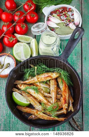 Fried smelt in the pan on the table with a sauce lime tomatoes dill and garlic. A traditional Russian dish