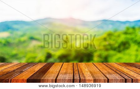 Wood Table And Blur Image Of Green Mountain.
