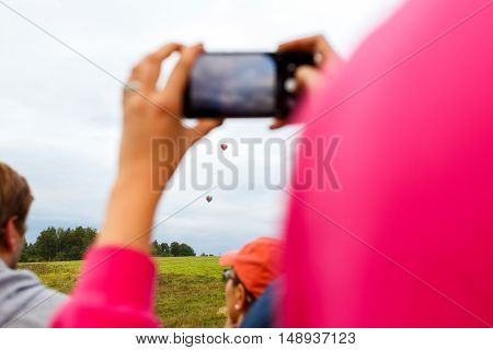 Woman while locating on land taking photo of hot air balloon on phone camera
