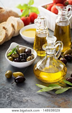 Olive oil in vintage bottles with black and green olives and italian cuisine ingredients on rustic background