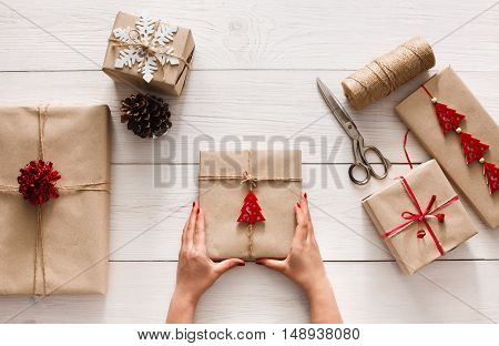 Creative hobby. Woman's hands show christmas holiday handmade present in craft paper with twine ribbon. Scissors and boxes with bows and snowflakes on white wooden table, top view.