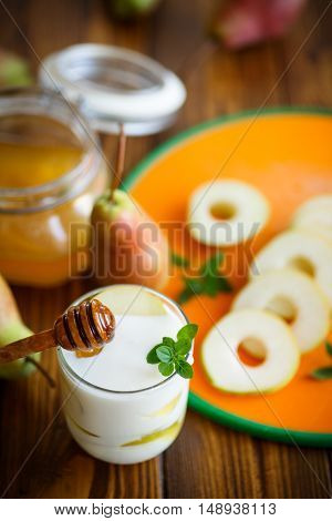 sweet pears with yogurt and honey in a glass