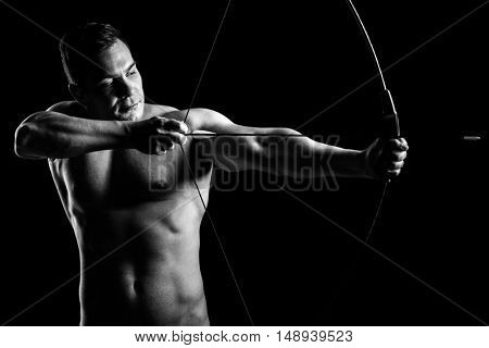 Shirtless guy aiming with a bow and arrow isolated on black background