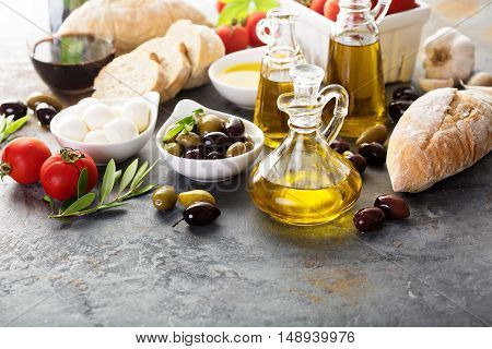 Olive oil in vintage bottles with black and green olives and italian cuisine ingredients copyspace on rustic background