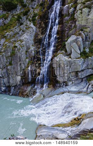 Waterfall On Rocky Mountains In Switzerland