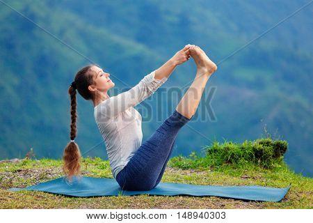 Yoga exercise outdoors -  woman doing Ashtanga Vinyasa Yoga balance asana Ubhaya padangusthasana Big Double Toe Yoga Pose in Himalayas in India