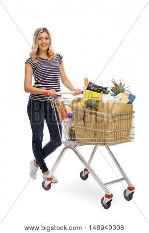 Full length portrait of a woman posing with a shopping cart full of groceries isolated on white background