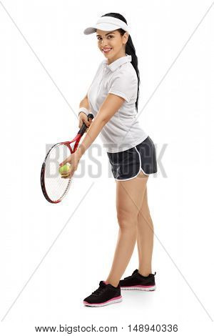 Full length portrait of a female tennis player preparing to serve isolated on white background