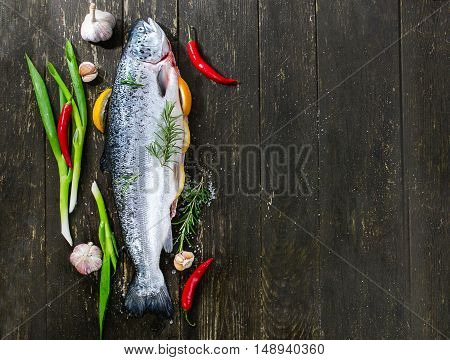 Raw Salmon With Herbs And Spices On Dark Rustic Background.