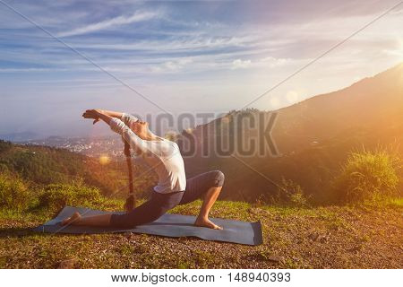 Yoga outdoors - sporty fit woman practices yoga Anjaneyasana - low crescent lunge pose outdoors in mountains in morning. With light leak and lens flare