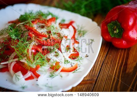 fresh salad with fresh peppers and onions on a wooden table