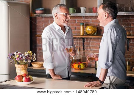 Cheerful. Aged grey man sharing their news while having whiskey at the kitchen table