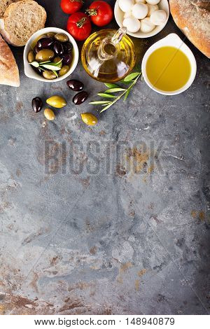 Olive oil in vintage bottles with black and green olives and italian cuisine ingredients copyspace overhead shot
