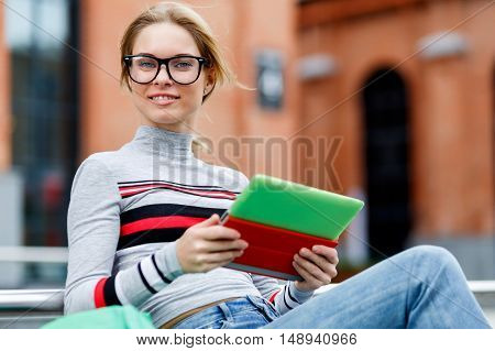 Young woman sits on street with tablet in hands opposite Red building