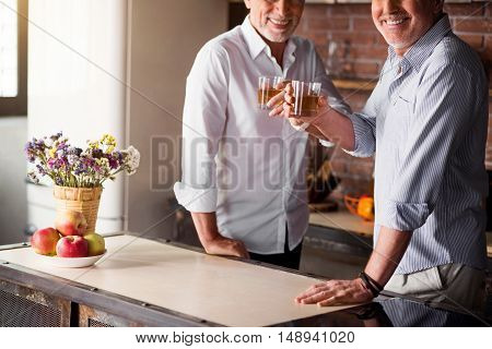 Glad and happy. Middle-aged males smiling at the camera while having their whiskey