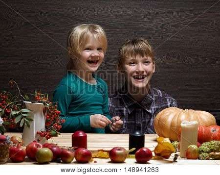 Children are prepared to meet the autumn holiday Halloween. Two sisters at the table. Pumpkin rowan tree decorations for the holiday. Laughter joy emotion