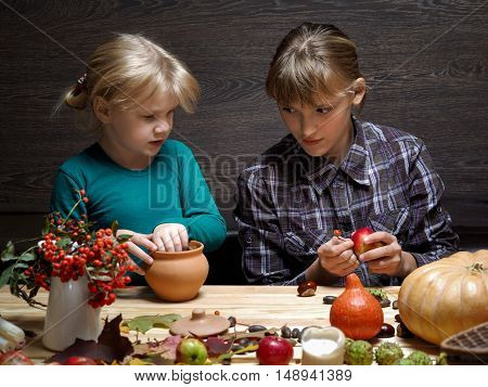 Busy kids preparing decoration for the Halloween holiday. Two sisters - junior and senior at the table. On the table pumpkins acorns. Preparation for the holiday