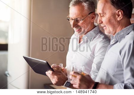 Parting after working. Two handsome men in white shirts looking at the tablet, chatting and having drinks