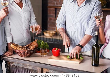 Vivid memories. Man's hands cutting vegetables while other family members drinking and standing around the table