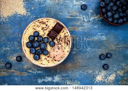 Gluten free amaranth and quinoa porridge breakfast bowl with blueberries and chocolate over vintage blue background. Top view overhead flat lay. Copy space