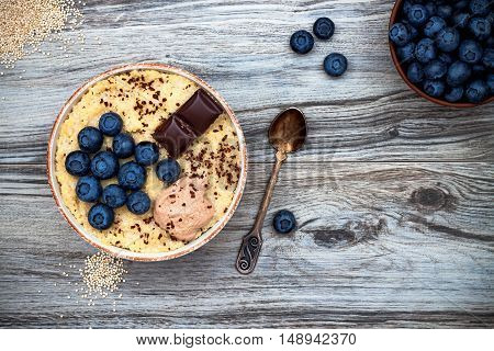 Gluten free amaranth and quinoa porridge breakfast bowl with blueberries and chocolate over rustic wooden background. Top view overhead flat lay. Copy space