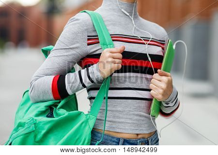 student with backpack and tablet in her hands on blurred background