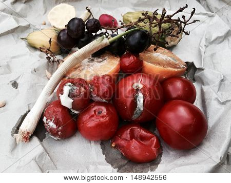 Different sorts of rotten fruit and vegetables on grey paper