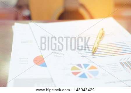 Document Chart And Yellow Pen On Brown Wood  Table With Guitar Background