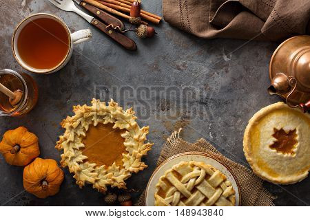 Homemade pumpkin pies decorated with fall leaves copyspace overhead shot