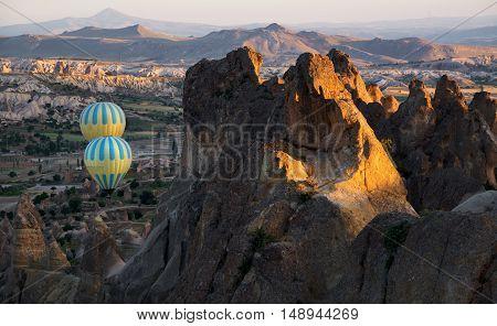 Bright and multicolored hot-air ballons fly between rocks. Cappadocia morning scene.