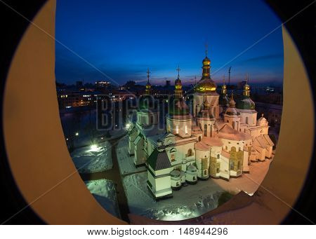 Evening view of Saint Sophia's Cathedral (Ukraine Kiev) through elliptical window. Church roof and land are covered with snow.