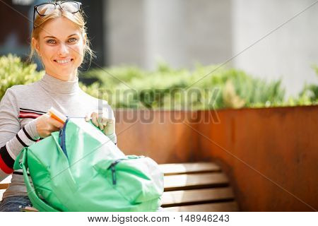 girl with backpack in hands of sitting on bench in afternoon