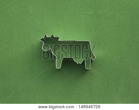 Cow wireframe silhouette with shadows on a green rough background