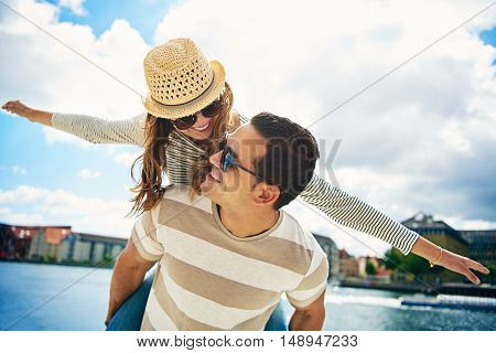 Loving young couple at an urban waterfront having fun laughing a piggy back riding with outstretched arms imitating an airplane