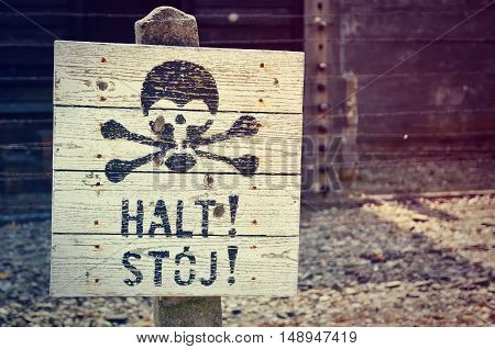 OSWIECIM POLAND - MAY 12 2016: Sign warning of the danger of the fence in concentration camp Auschwitz-Birkenau in Oswiecim Poland.