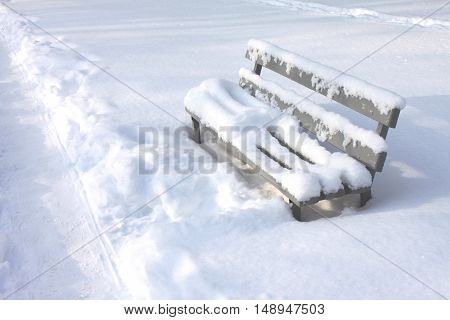 Snow-covered bench in city park between snow drifts in winter