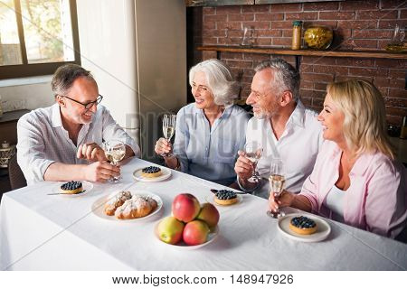 Friends and family gathering around the table to bring birthday greetings to retired man and drink wine together