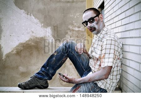 a scary zombie wearing ragged clothes and black plastic-rimmed eyeglasses using a smartphone