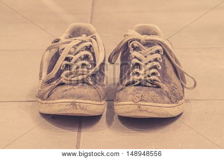 Muddy sneaker shoes with laces in sepia color