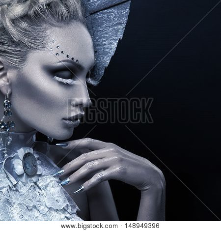 Closeup portrait of beautiful young woman dressed as winter queen. Creative makeup. Over black background. Copy space.