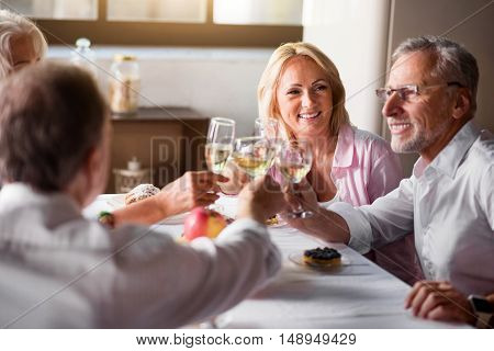 Celebrating. Smiley group of white people cheering with white wine while having a party