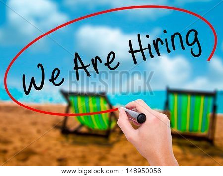 Man Hand Writing We Are Hiring  With Black Marker On Visual Screen