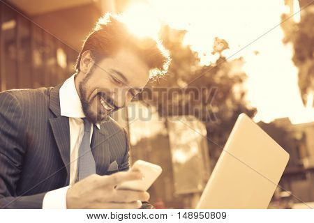 Smiling manager using his smartphone