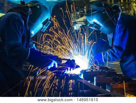 Team welder welding  Industrial automotive part in car production factory