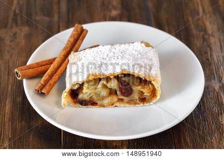 Apple strudel with icing sugar, cinnamon sticks, raisins, wooden background