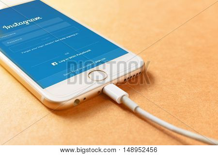 LAMPHUN THAILAND - AUGUST 15 2016: Screen shot Instagram application using Iphone6 charging with power bank on wood board. Instagram is largest and most popular photograph social networking.