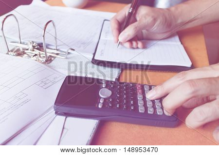 Soft focus close up of man with using counting making notes with calculator at home hand is writes in a notebook with books savings finances economy and home concept.
