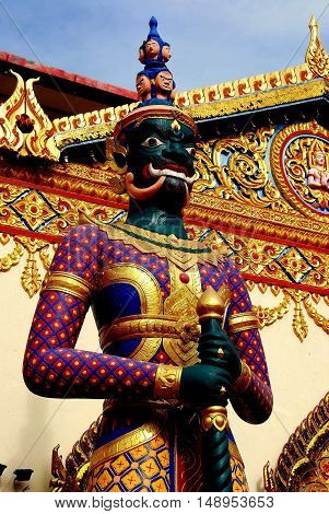Georgetown Malaysia - January 8 2008: Giant demon guardian with a hat of 8 faces stands in front of the entrance to the c. 1900 Wat Chaiyamangalaram Thai Buddhist Temple