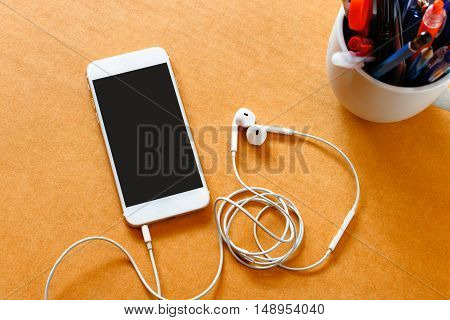 Smartphone with blank screen and earphones on wooden background