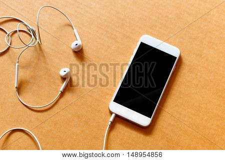 Blank white smartphone and earphones on wooden background